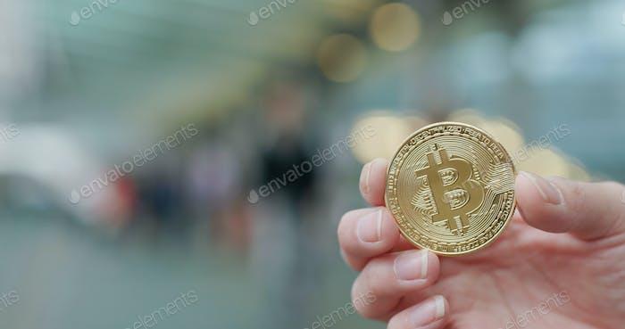 Hand hält Bitcoin in der Stadt im Freien