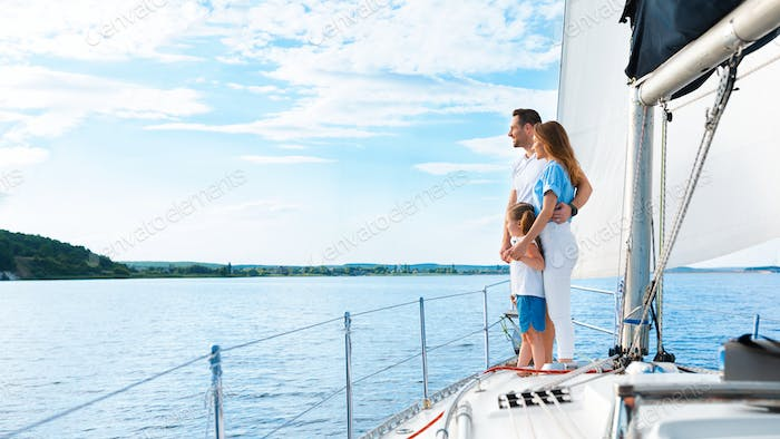 Family Of Three Enjoying Yacht Ride Standing On Boat Outdoors
