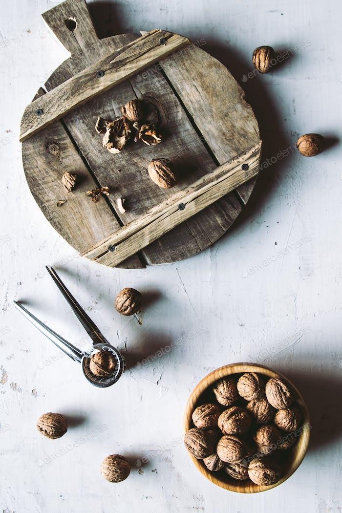 Nueces en cuenco de De madera sobre mesa con Cascanueces