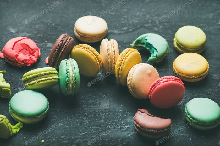 Colorful French macaroons over black background, selective focus