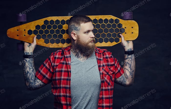 Bearded man with tattooes on his arms.