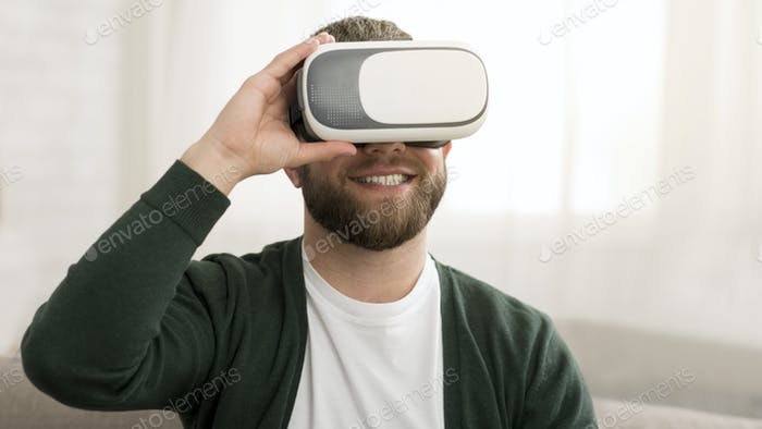 Joyful middle aged man trying vr glasses at home