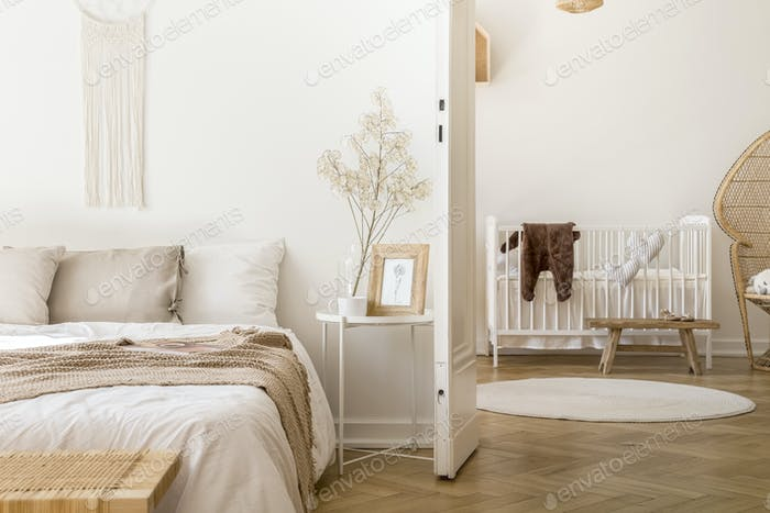 Real photo of white bedroom interior with bedside table with pla