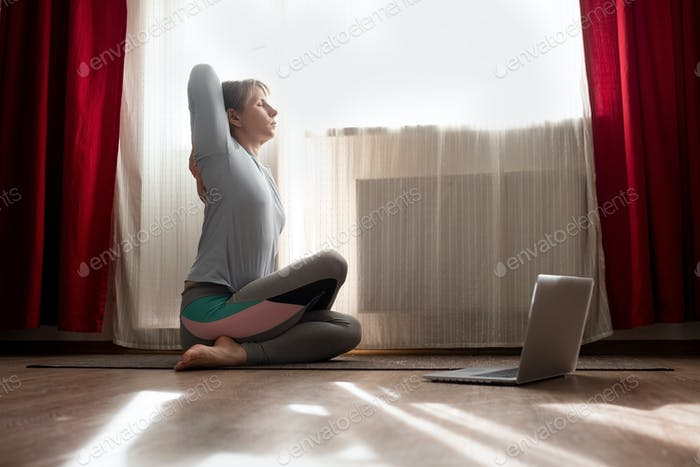 Woman in sitting yoga pose cow face asana during online lesson on laptop.