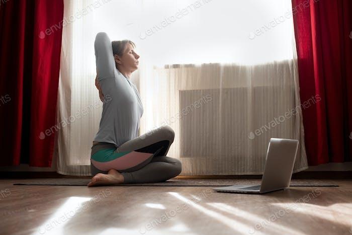 Frau im Sitzen Yoga Pose Kuh Gesicht asana während der Online-Lektion auf Laptop.