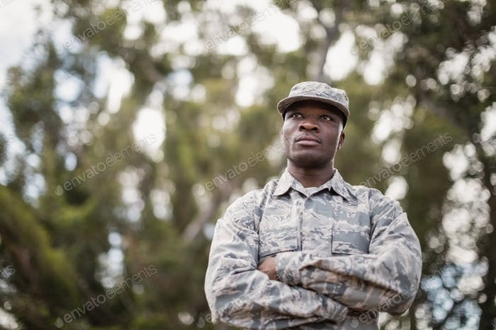 Thoughtful military soldier standing with arms crossed