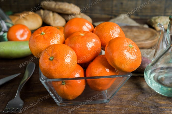 group of tangerines in glass bowl on classic rustic wood