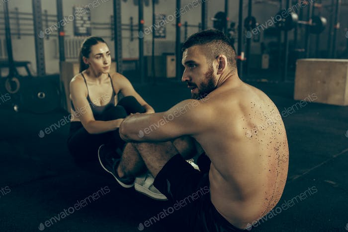 Man and woman during exercises in the fitness gym. CrossFit.