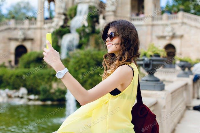 Brunette girl is making selfie-portrait on sightseeing background. She wears yellow T-shirt