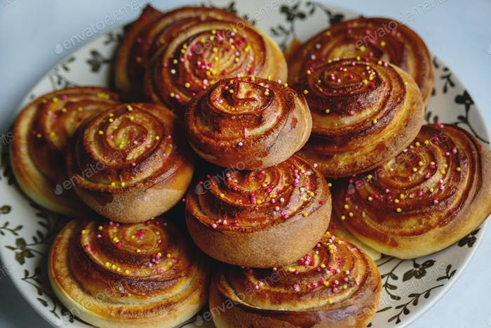 sweet baked rolls buns with cinnamon and colorful sprinkle