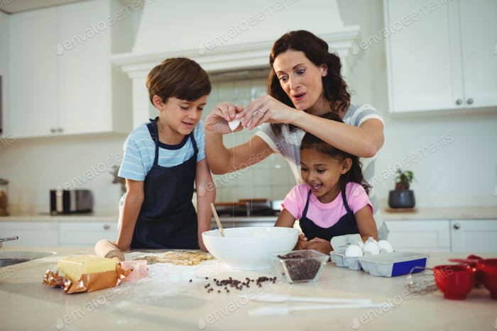 Mother and kids breaking egg in the bowl while preparing cookie