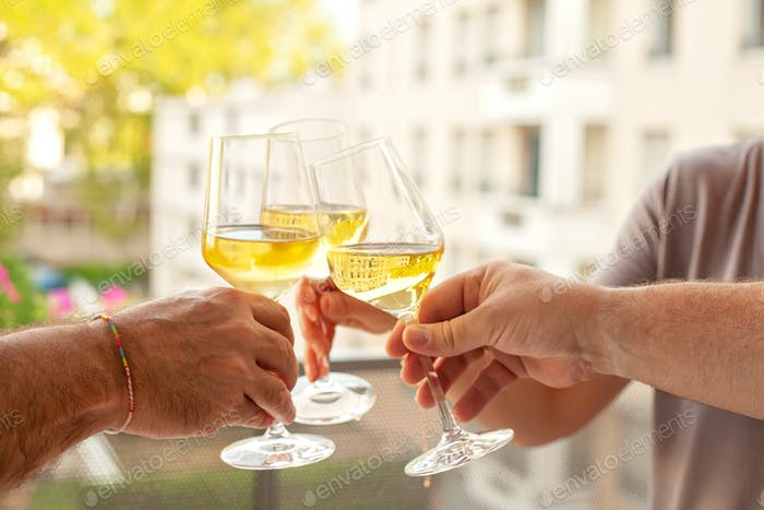 People hands cheering with white wine glases on the terrace