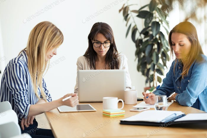 Pretty young businesswomen working of new ideas in co-working space.