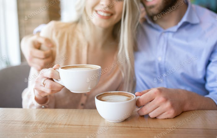 Cropped view of romantic couple drinking coffee and hugging at cafe