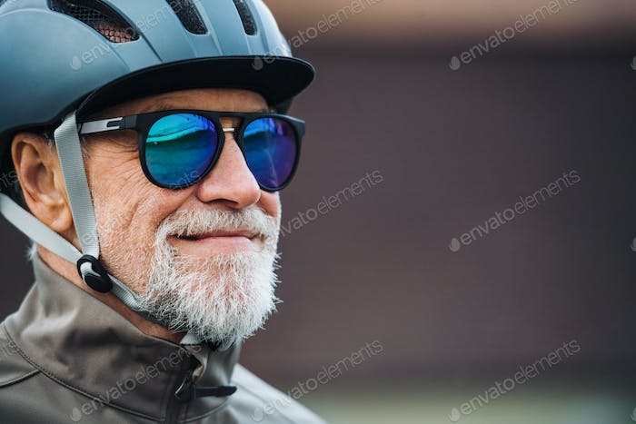 Close-up of active senior man with sunglasses and helmet standing outdoors. Copy space.