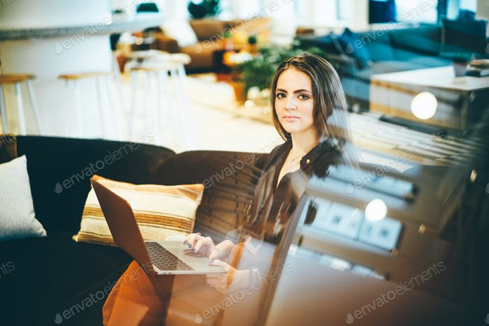 Businesswoman working on laptop in modern coworking. Business concept.