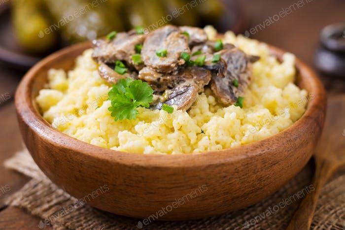 Millet porridge with mushrooms in a wooden bowl