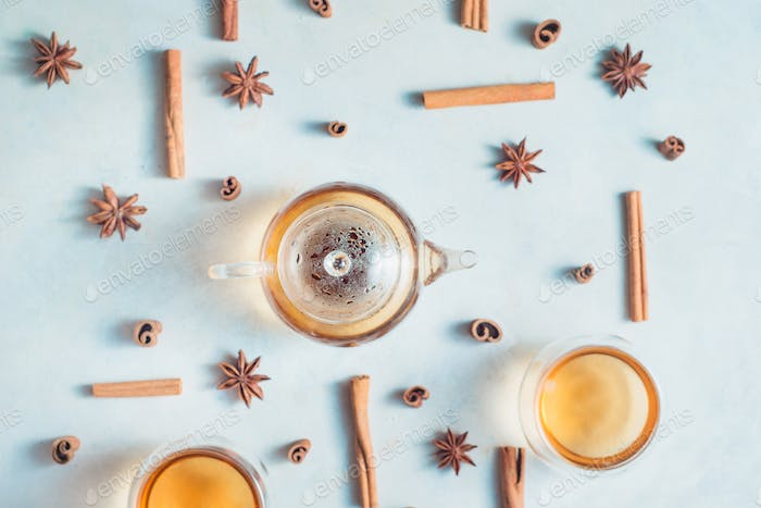 Creative tea arrangement with cinnamon, anise stars, teapot and tea bowls on a white background with