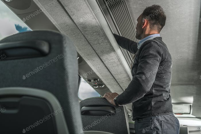 International Coach Bus Passenger Securing Luggage Inside Vehicle