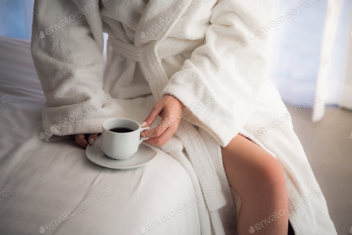 Close-up of legs of woman in white terry bathrobe on bed with cup of coffee in the morning. Ideal