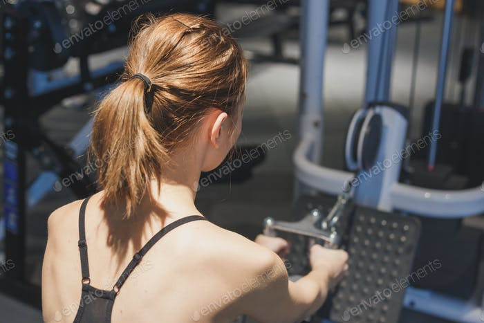Girl in the gym develops the muscles of the back.