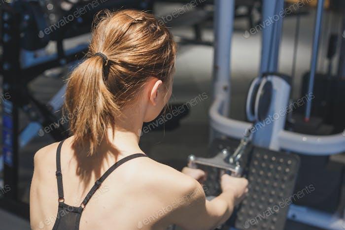 Chica en el gimnasio desarrolla los músculos de la espalda.