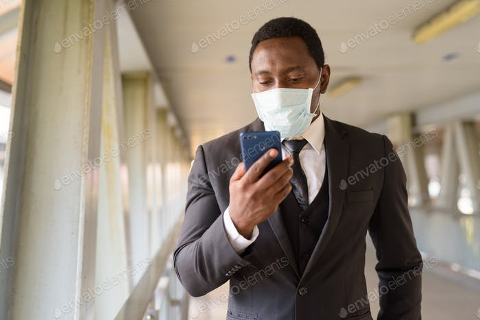 Portrait of African businessman with mask using phone at the footbridge