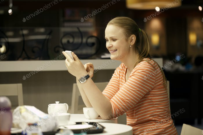 Young woman chatting on smartphone in cafe