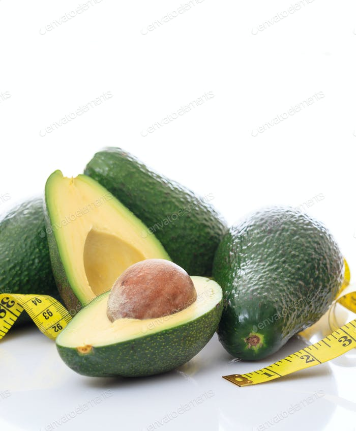 Healthy lifestyle concept. Avocados whole and half and measure tape on white background