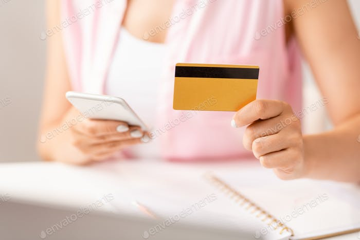 Hand of female shopper with plastic card using smartphone to make online order
