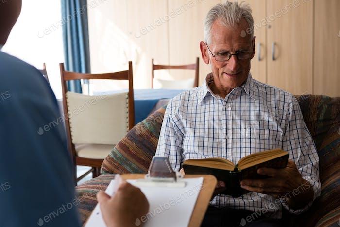 Doctor escribiendo en Papel mientras que el Hombre mayor leyendo Libro en el Página de inicio de ancianos