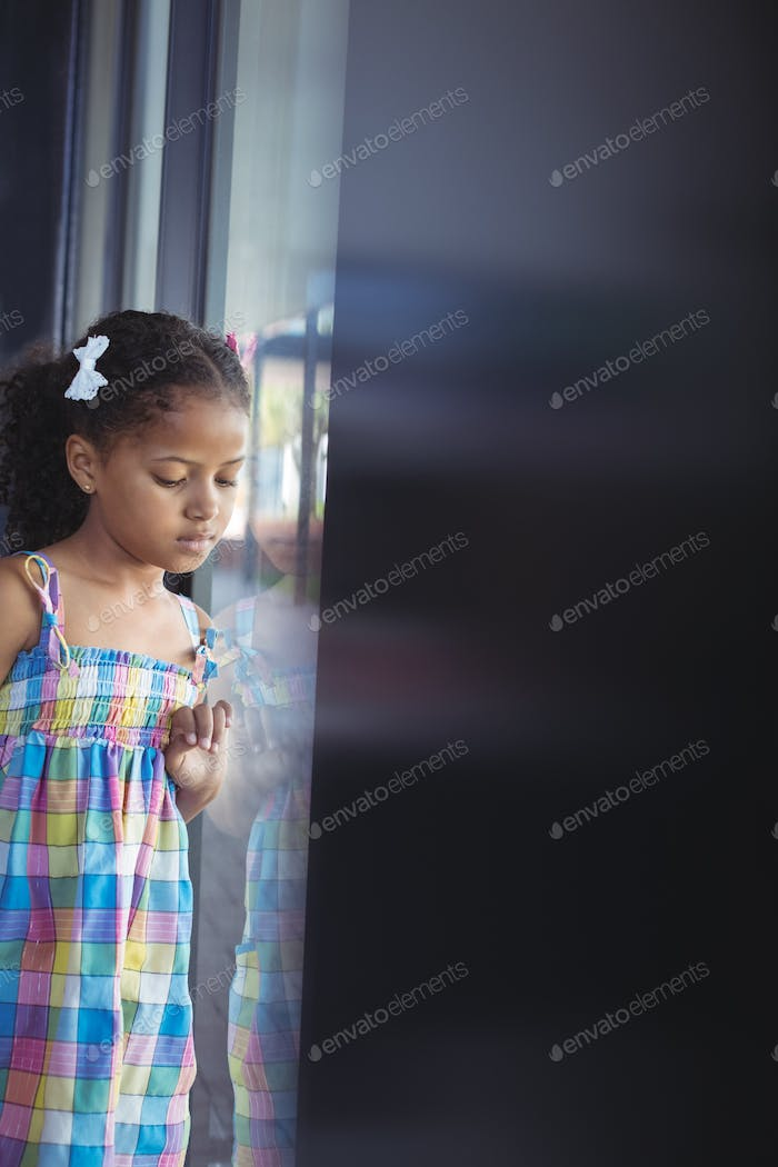 Girl looking down while standing by window