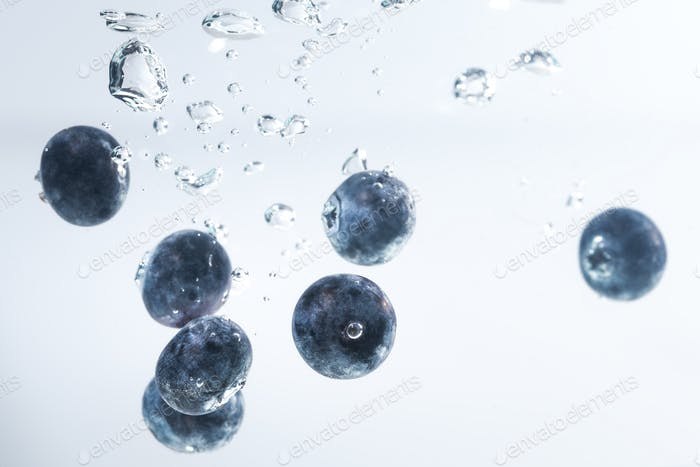 Organic Blueberries sinking into water with air bubbles