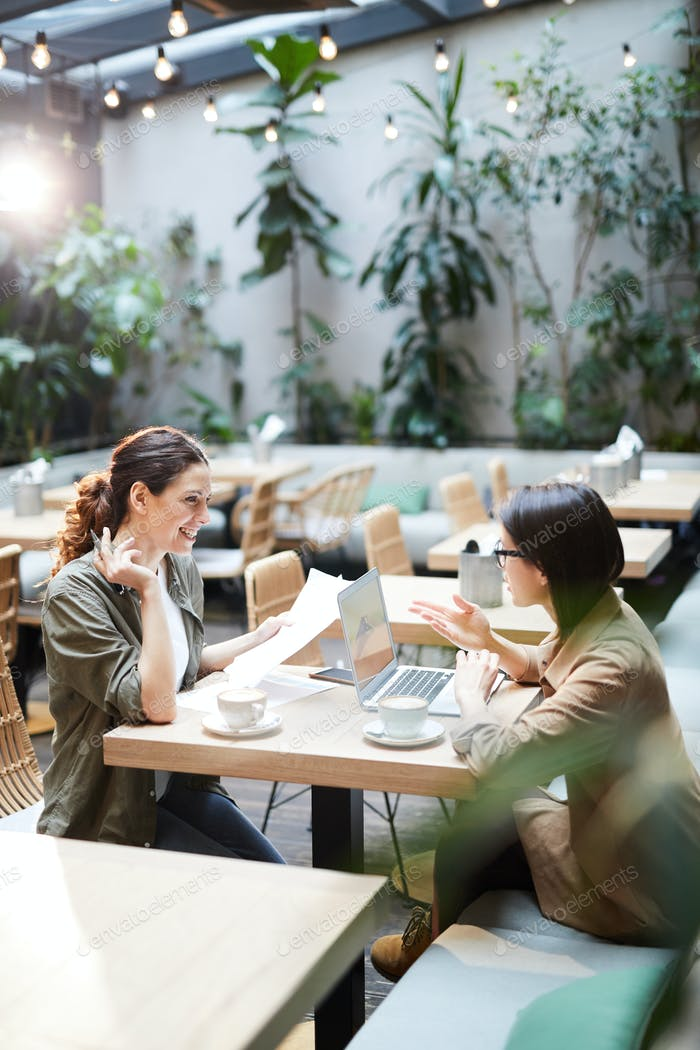 Positive women analyzing report in cafe