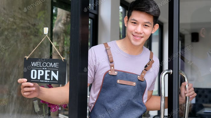 Young asian barista open a glass door to welcome customers.