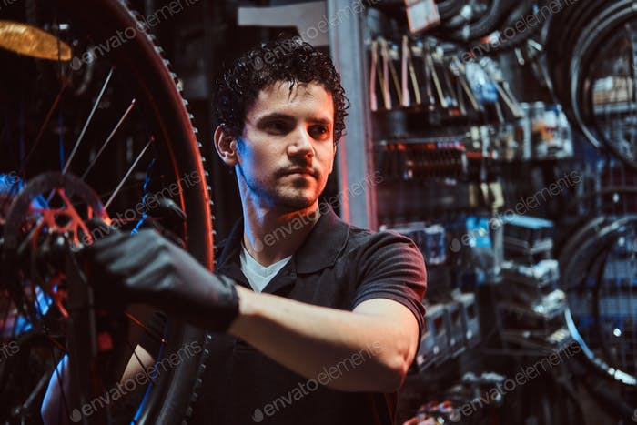 Handsome diligent master is fixing bicycle's wheel at his workplace