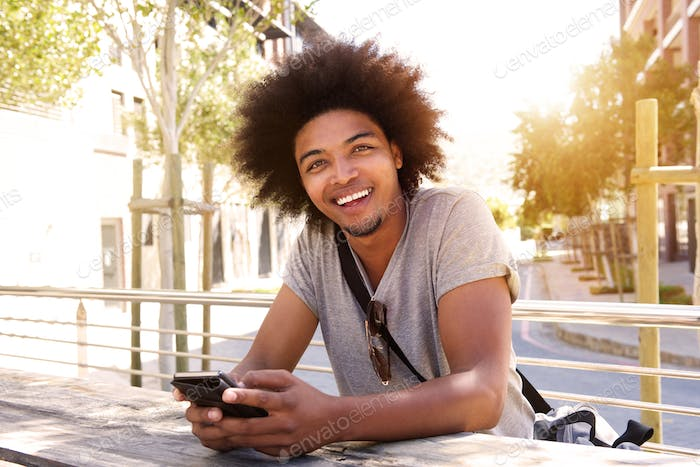 Smiling young man with cellphone sitting outside