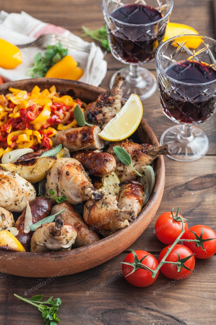 Chicken legs roasted with sausages and vegetables.