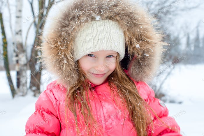 Portrait of little adorable girl in snow sunny winter day