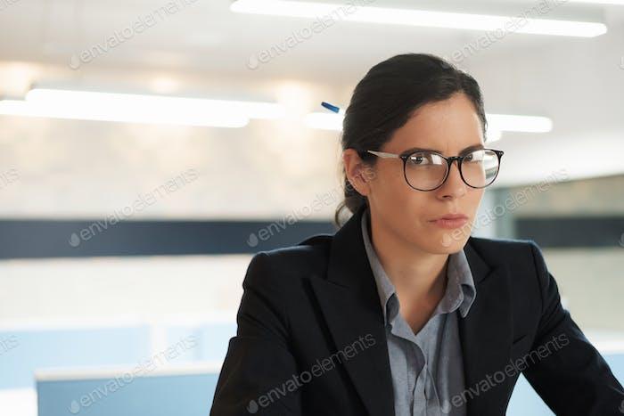 Портрет Сильная несчастливая Серьезная Бизнесвумен смотрит на камеру в офисе