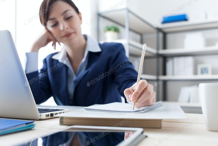 Businesswoman writing notes on a notebook