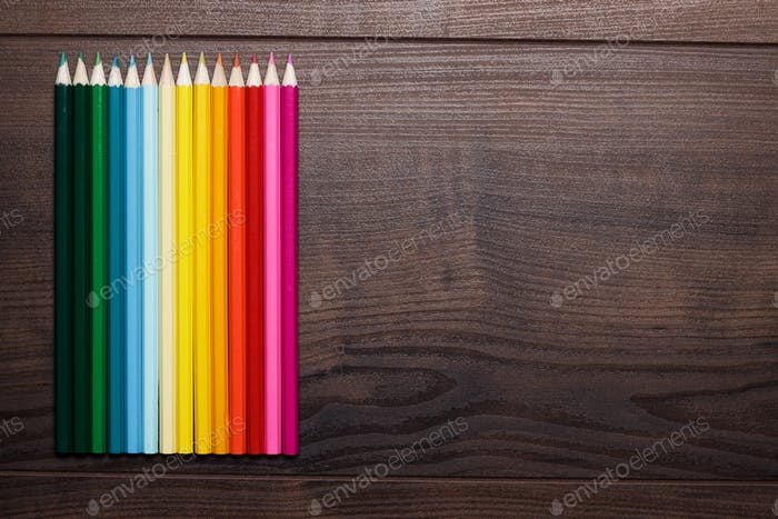Colorful Pencils Over Brown Wooden Table Background