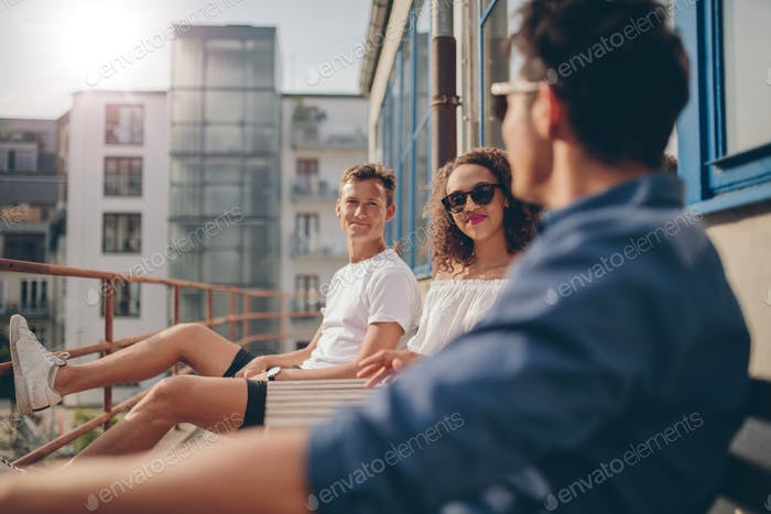 Group of young people relaxing in a balcony