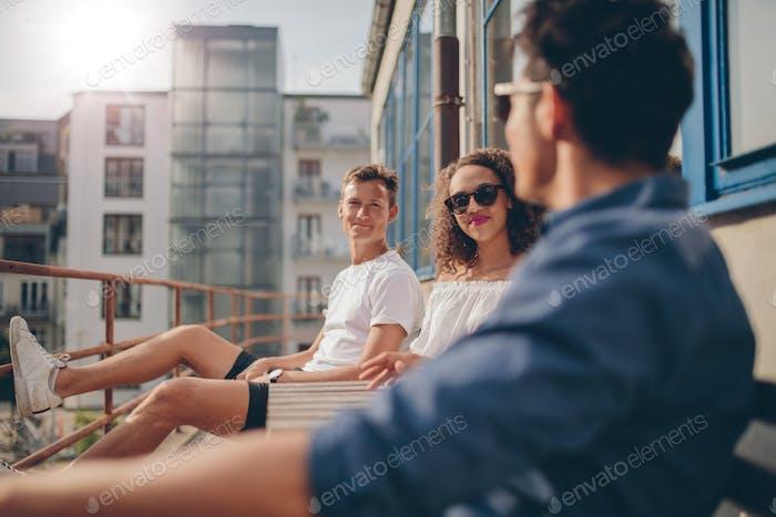 Gruppe von Jugendlichen entspannen auf einem Balkon