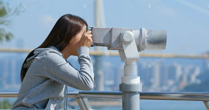 Tourist look at the binocular for seeing the view in Hong Kong