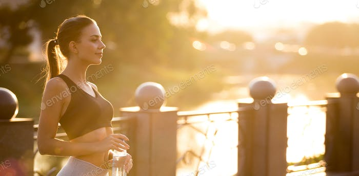 Serene girl athlete enjoying sunrise, training early in morning