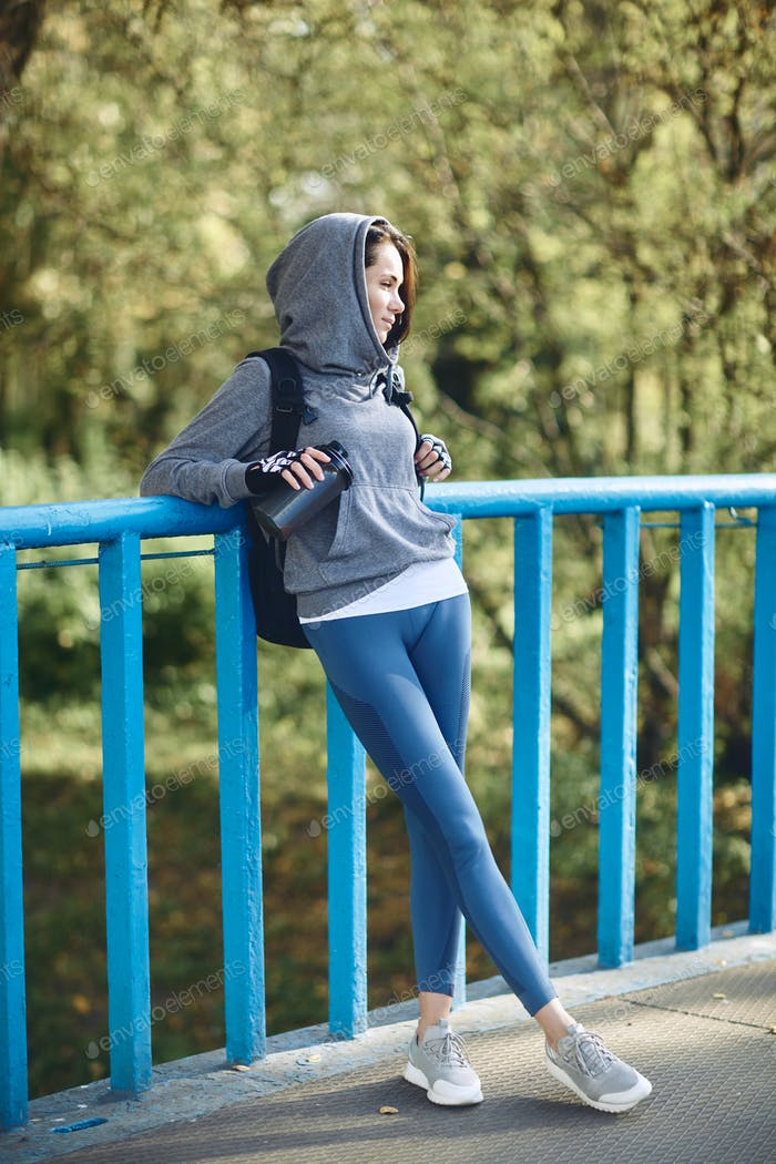 A brunette girl in a hoodie in nature walks in the Park in autumn weather.