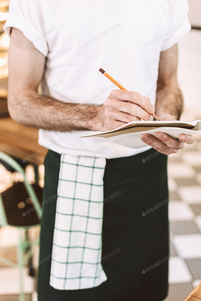 Close up photo of waiter standing with pencil and writing order in notebook in cafe