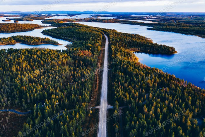 Aerial view of road through autumn forest with blue lakes in Finland.