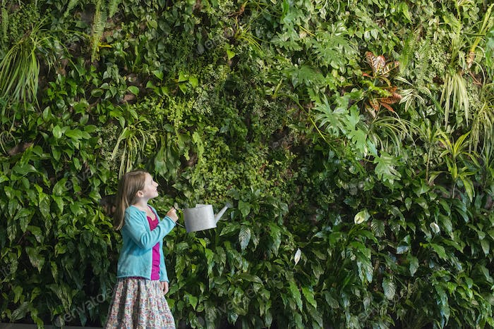 City in spring, A young girl standing in front of a wall covered with ferns and climbing plants,